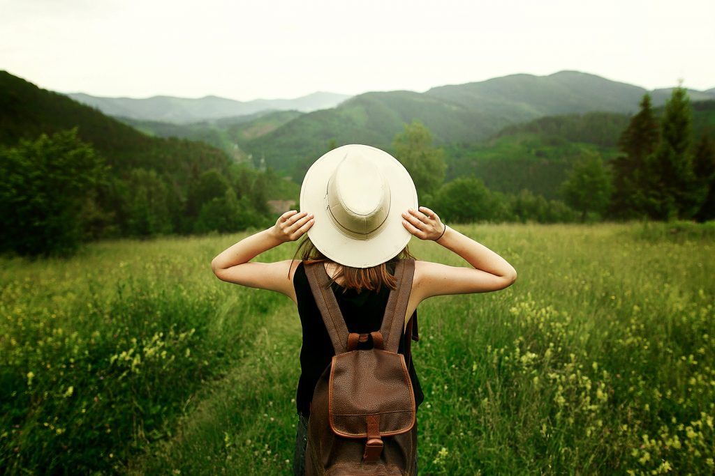 woman traveler with backpack holding hat and looking at amazing mountains and forest wanderlust travel concept space for text atmosperic epic moment - Forest Medical Equipment Calibration