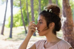 Young woman using asthma inhaler in the park - Forest Medical Equipment Calibration