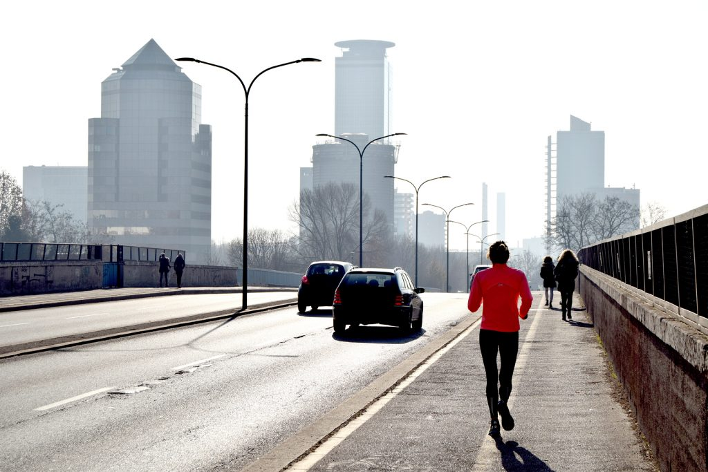A woman is training along the way of a big city. Asthmatic Allergenic and Triggers - Medical Equipment Calibration