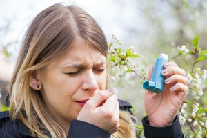 Picture of a young woman having pollen allergy holding a bronchodilator outdoor. Asthmatic Allergenic and Triggers - Medical Equipment Calibration