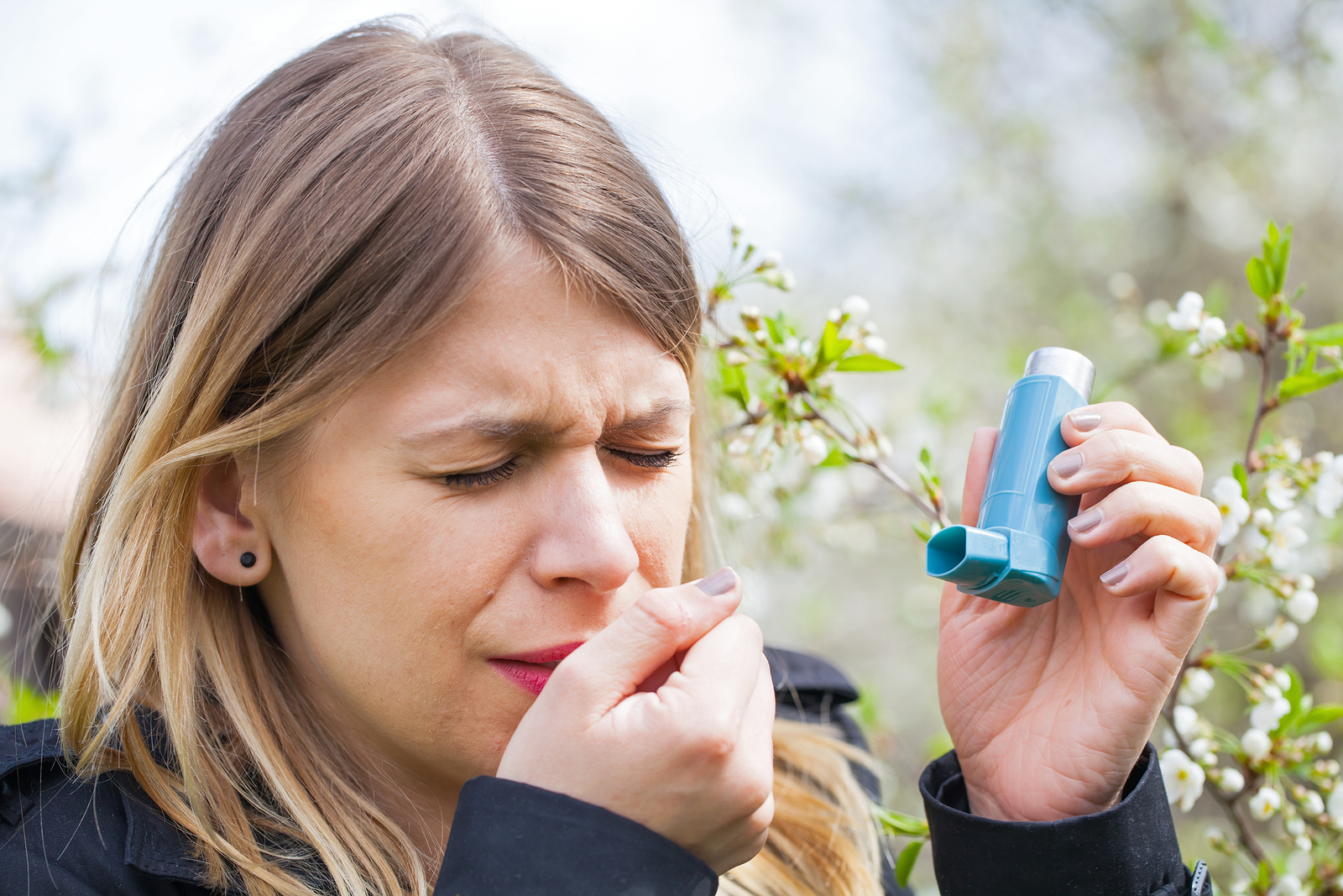 Picture of a young woman having pollen allergy holding a bronchodilator outdoor. Asthmatic Allergenic and Triggers - Medical Equipment Spirometer Calibration