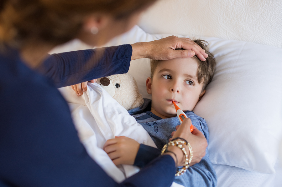 Sick boy with thermometer laying in bed and mother hand taking temperature. Mother checking temperature of her sick son who has thermometer in his mouth. Sick child with fever and illness in bed - Forest Medical Calibration Services