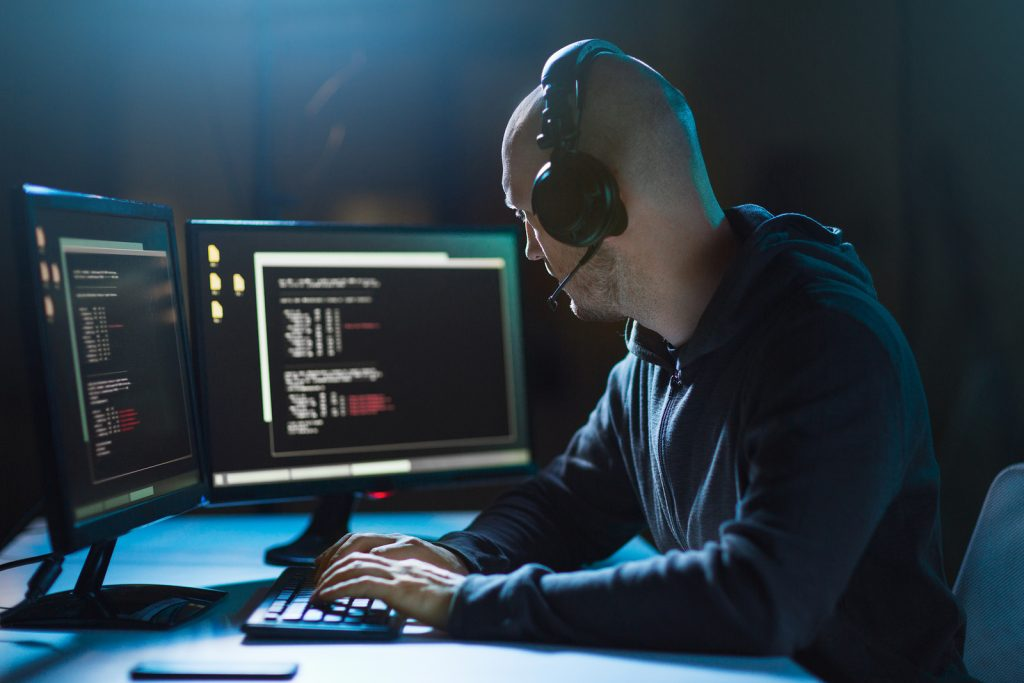 cybercrime, hacking and technology concept – male hacker with he