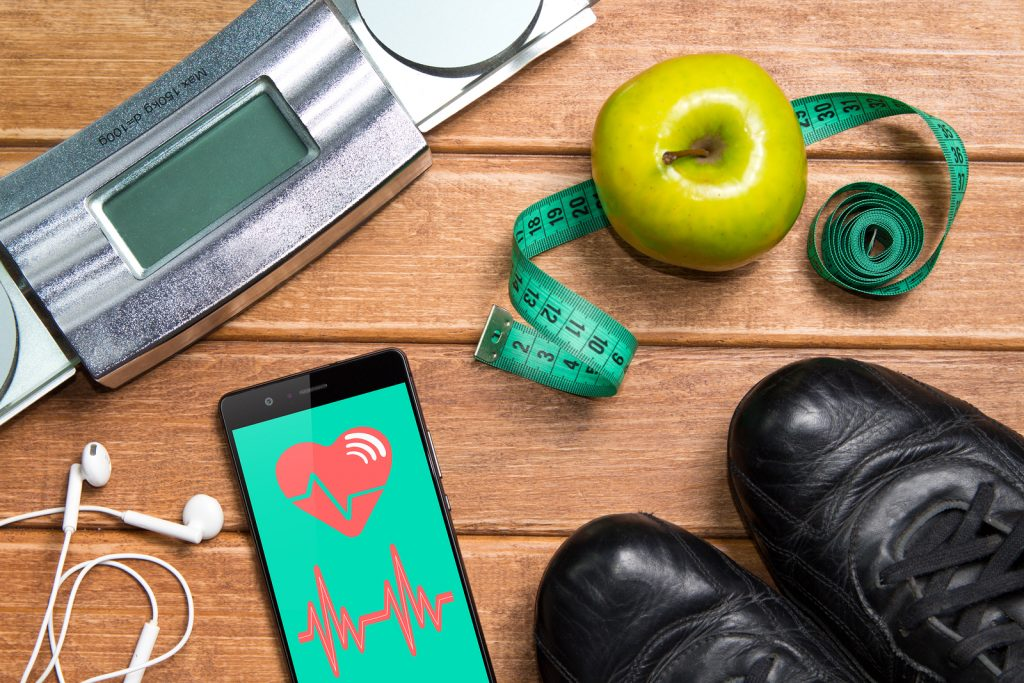 Sports Shoes , Apple , Scales, And A Phone With Health Card On A