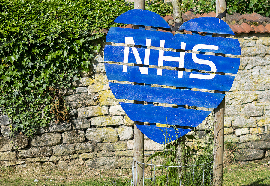 Heart Made Of Wood Painted Blue With The Letters Nhs In White.